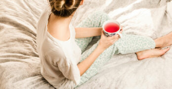 Woman Drinking Tea On Bed | Explaining The 6 Most Common Sleepy Time Tea Ingredients